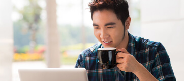 Man holding a cup of coffee using a laptop